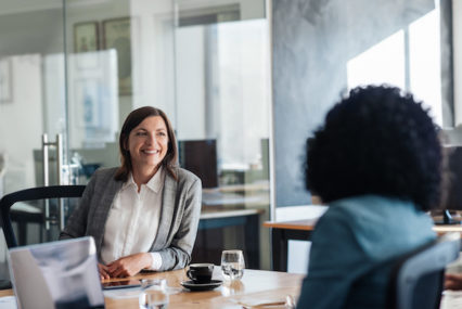 Two smiling young businesswomen talking together while sitting around a boardroom table in a modern office